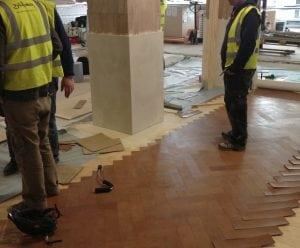 Workmen applying the leather floor panels.