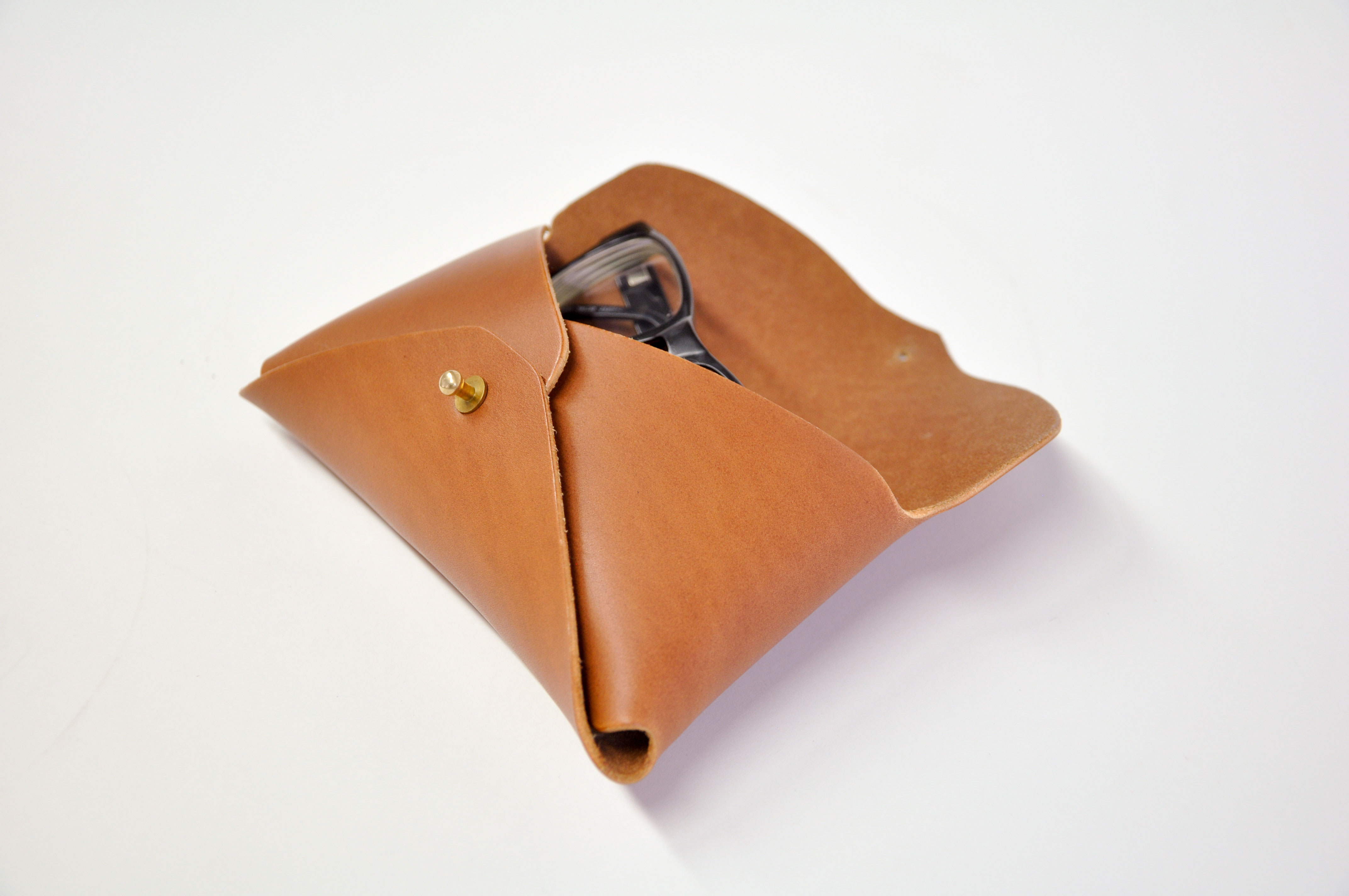 A leather glasses case with a pair of glasses inside.