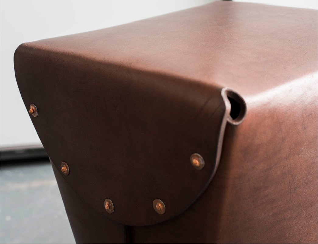 A leather stool with copper rivets.