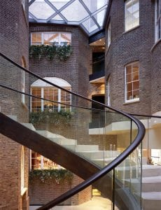 The helical staircase with a seamless leather handrail and glass balustrade.