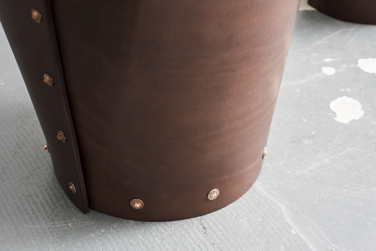 A closeup of the copper rivets fastening the leather of the stool.
