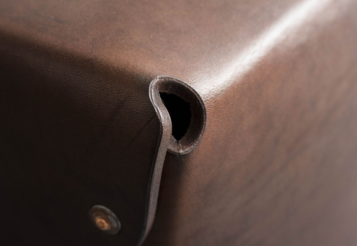 The neatly folded corner of a leather stool.