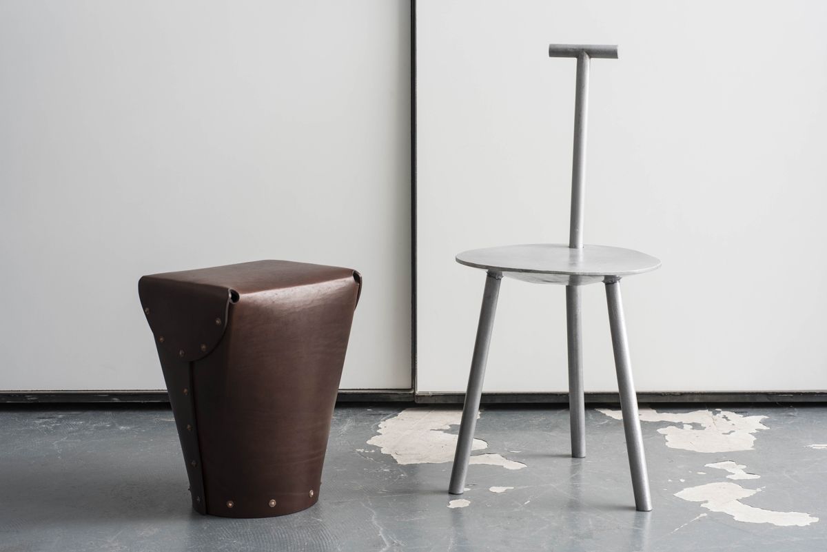 A leather stool next to an aluminium chair.