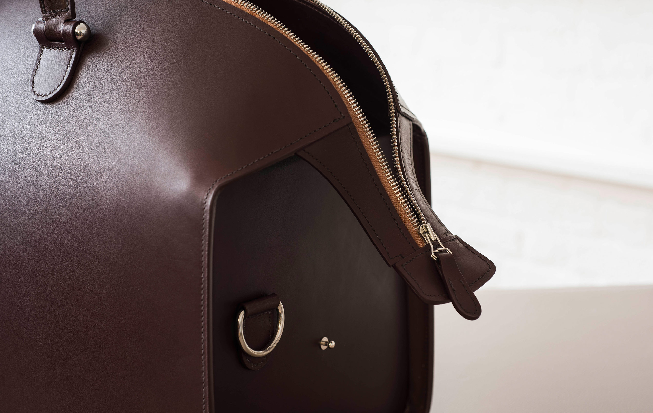 Focusing on the padded, hand-stitched zip and the soft texture of the leather flowing over the bag.