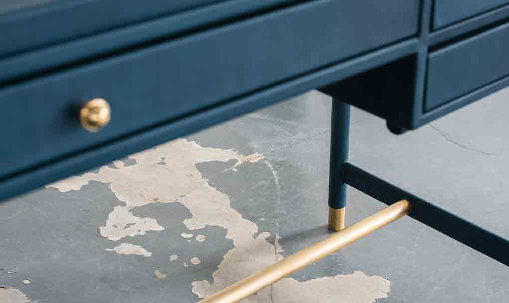 A focus on the brass frame of the desk.