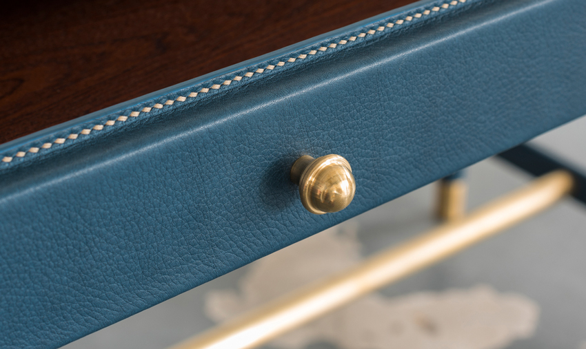 A close view of the leather-clad hardwood drawer and its fine accented detailing.
