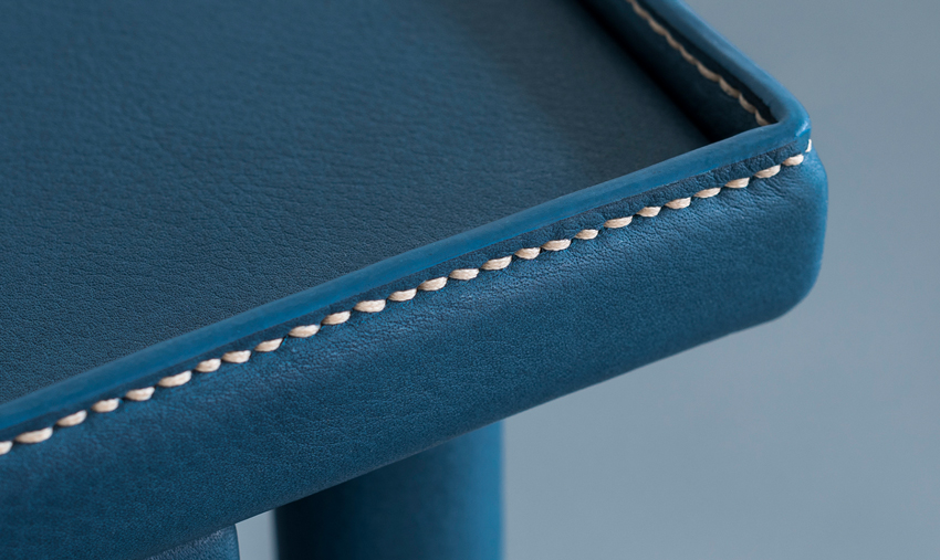 The stitching of the desk top, complete with petrol-blue leather.