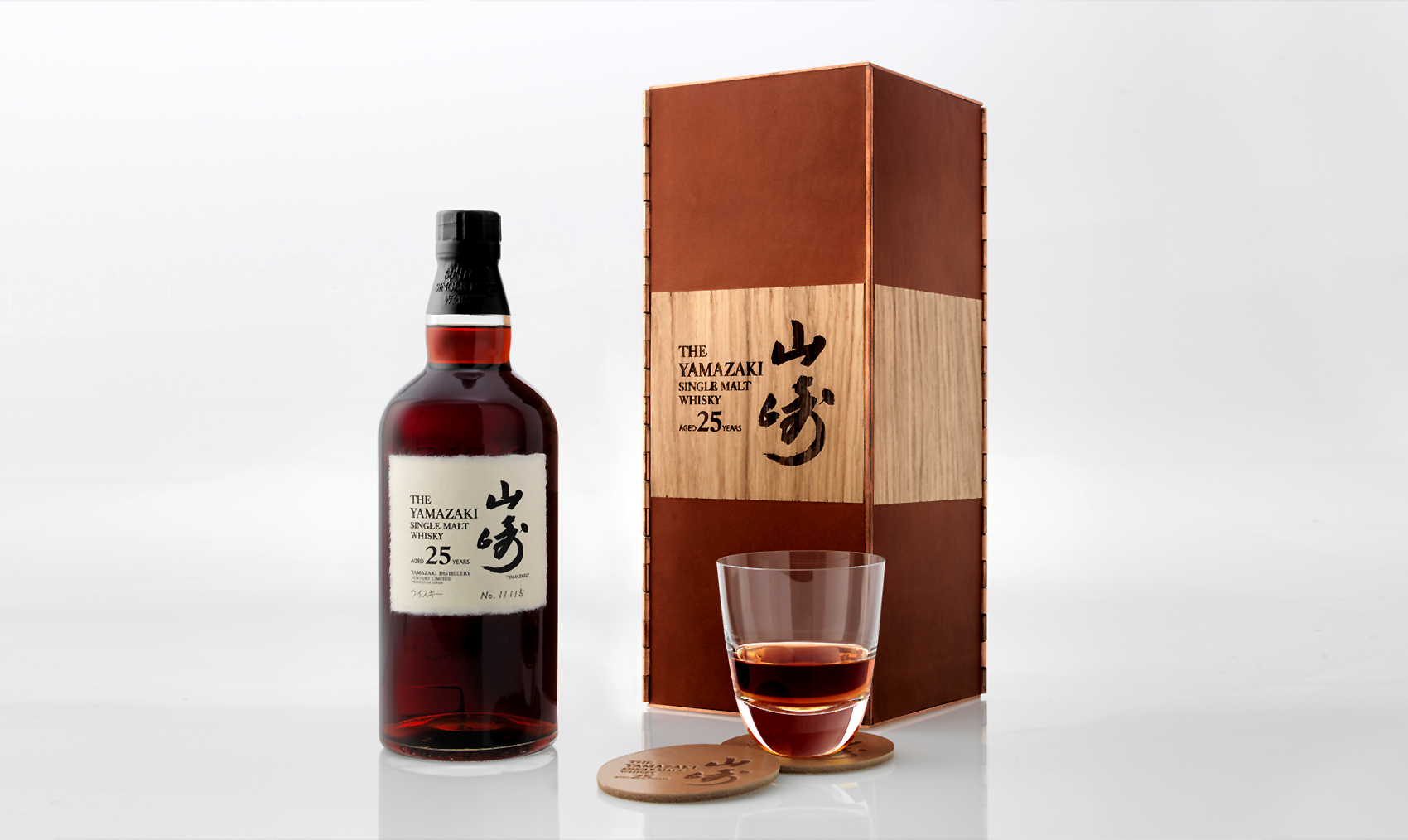 The whisky poured into a glass, beside its box and bottle.