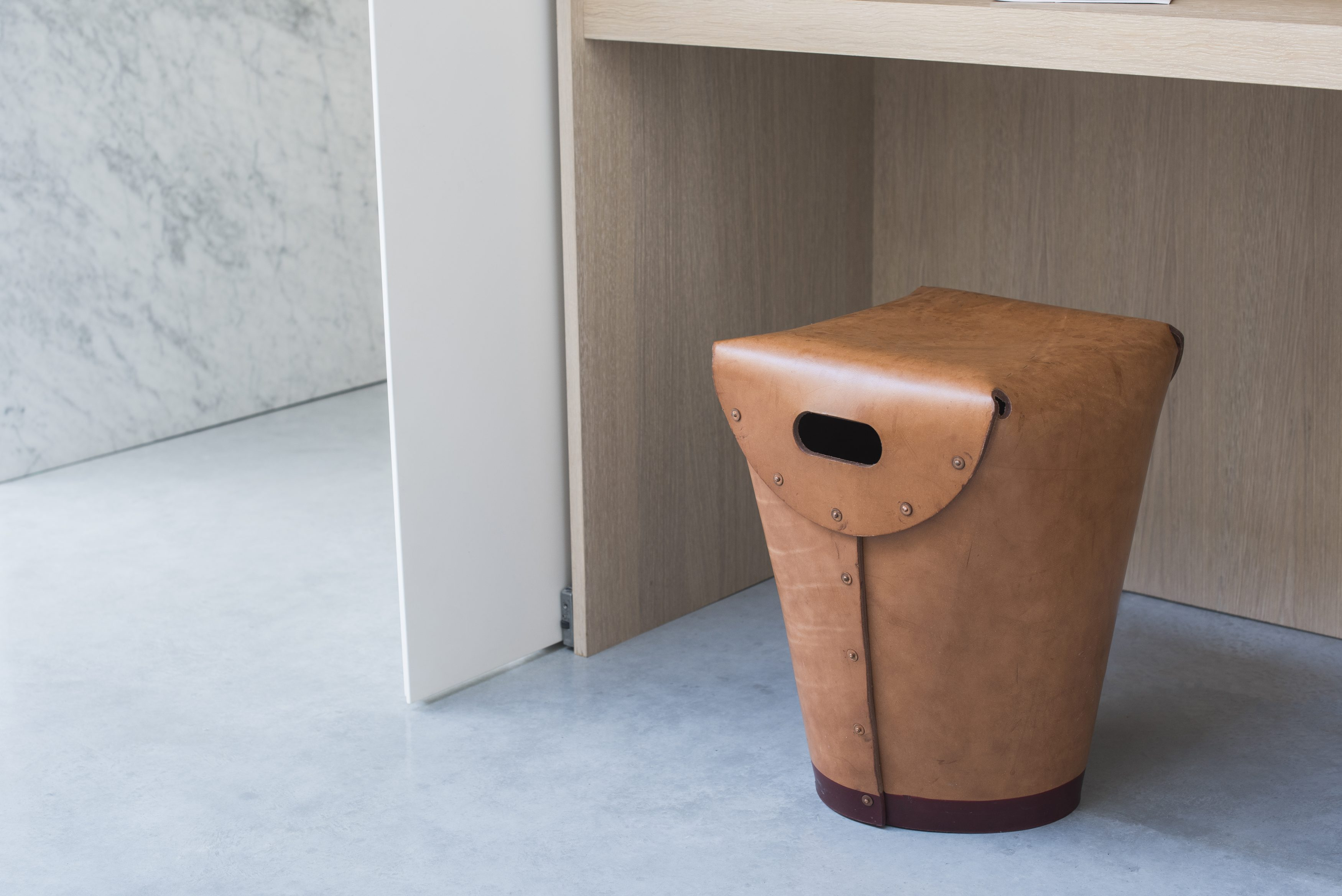 A vegetable-tanned leather stool with copper rivet detailing.