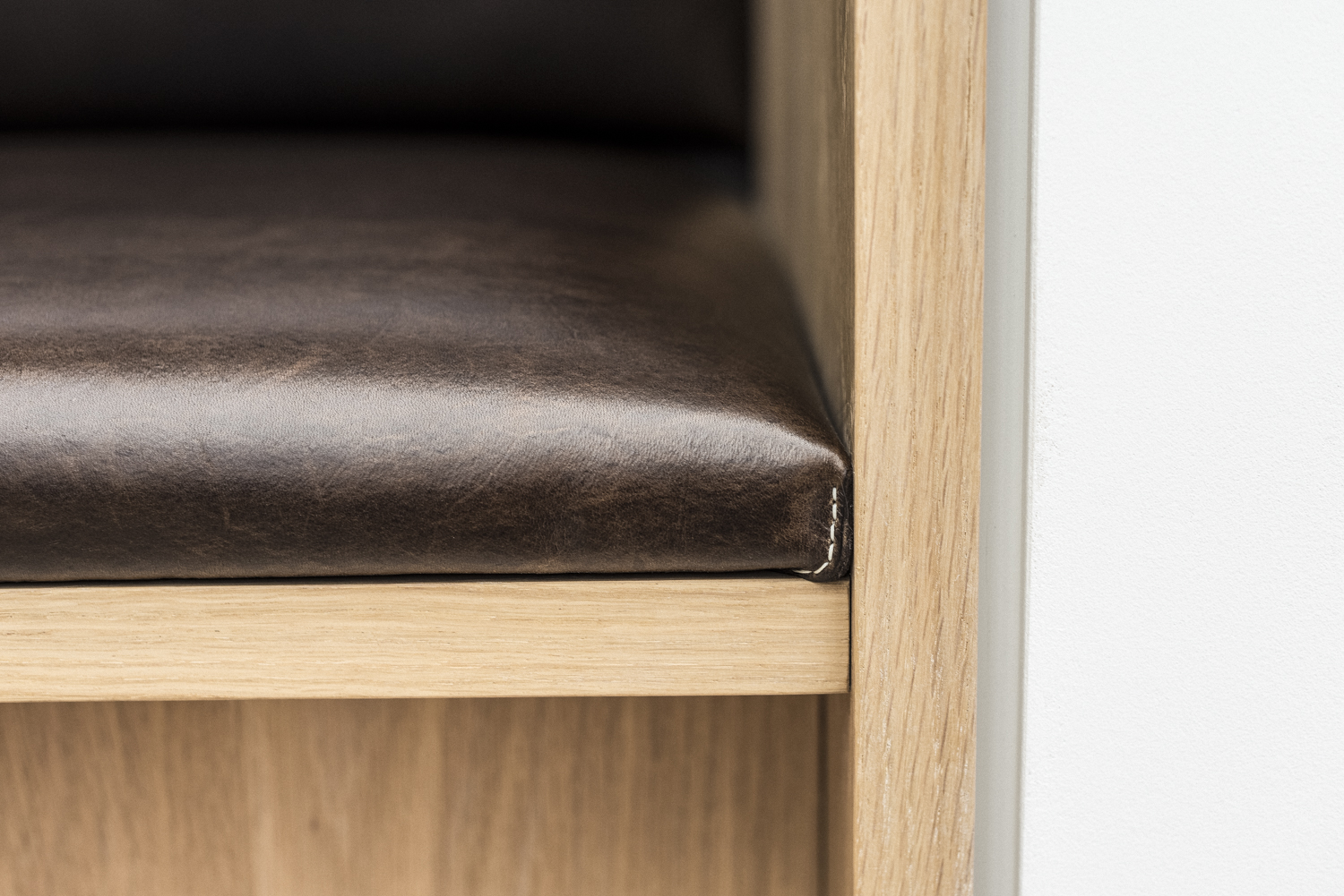 An extreme close up of the tanned leather seating, displaying the soft texture.