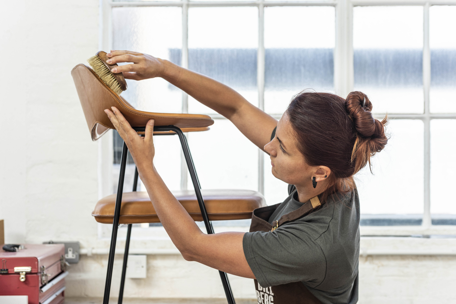 Woman brushing a tanned leather stool